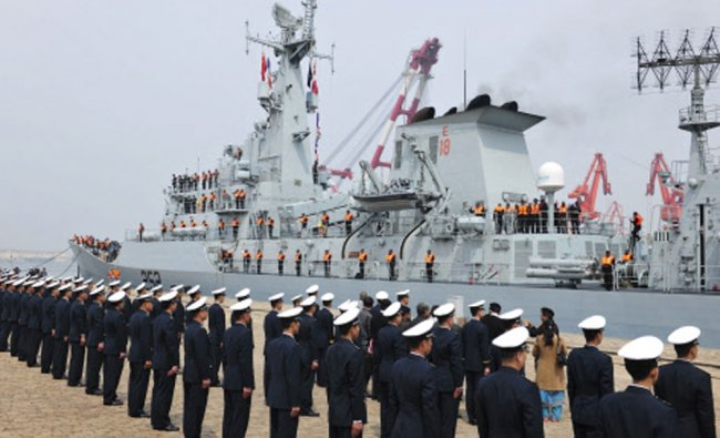 Chinese navy officers stand in formation as Pakistan naval frigate Shamsher arrives at a military...