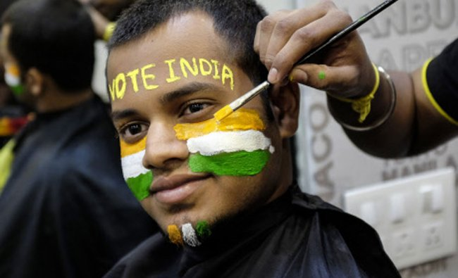 A man poses as he gets his face painted ahead of the sixth phase of India\'s general election...