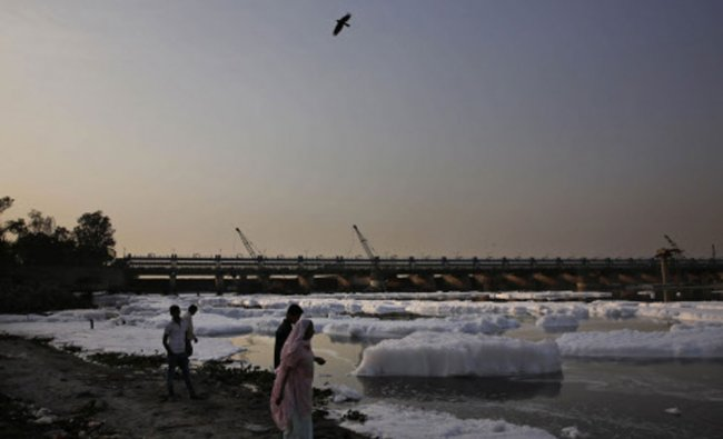 Indians stand on the banks of the River Yamuna, covered in industrial effluence on Earth Day in...