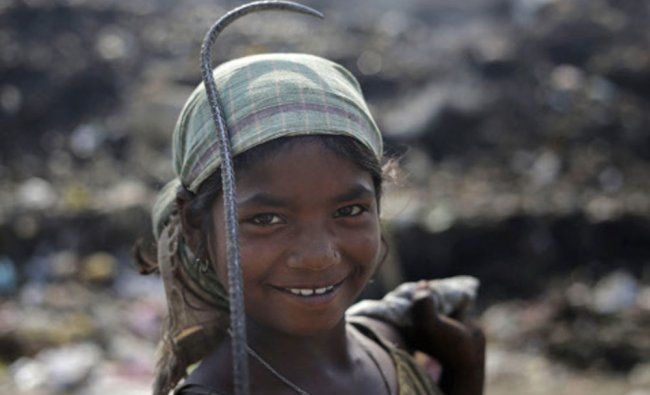 A ragpicker girl Zahanara Khatun, 12, looks at the camera as she searches for recyclable items at...