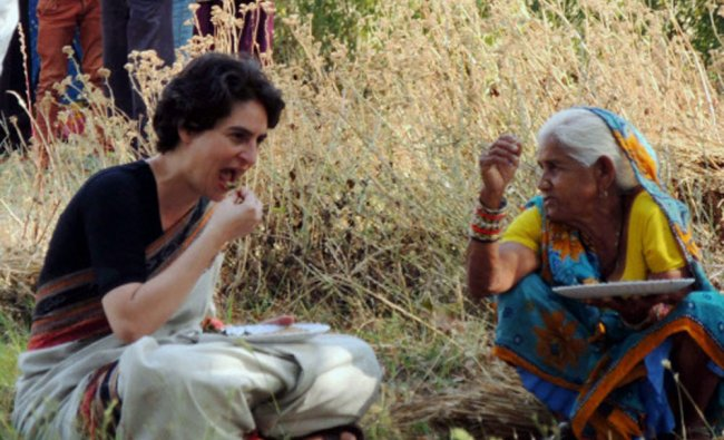 Priyanka Vadra shares meal with a village woman in a field during an election campaign for her...