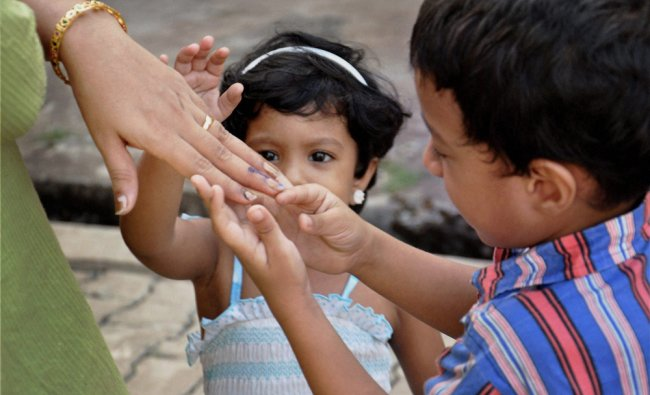 A woman voter showing inked finger to her children during repolling at a polling booth in Kochi...