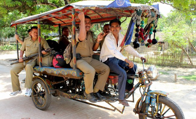 Police personnel ride a \'jugaad\' on their way to polling booths on the eve of Lok Sabha elections...