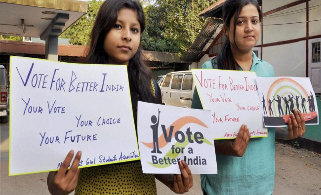 Girls display placards to create awareness on voting in Guwahati on Wednesday. PTI Photo