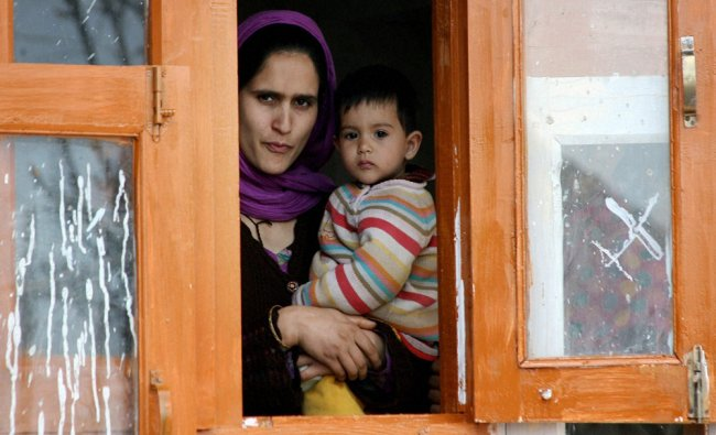 A woman with her son watches from a window the election campaign rally of National Conference...