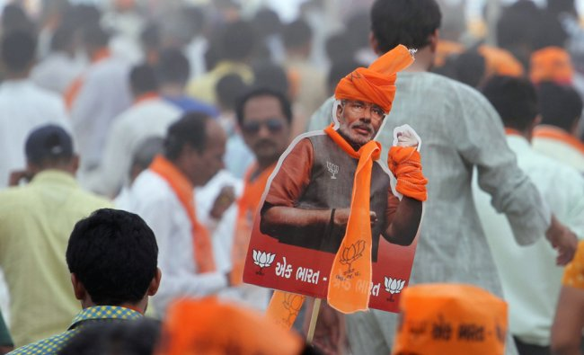 Supporter of Bharatiya Janata Party holds a cutout of prime ministerial candidate Narendra Modi ...