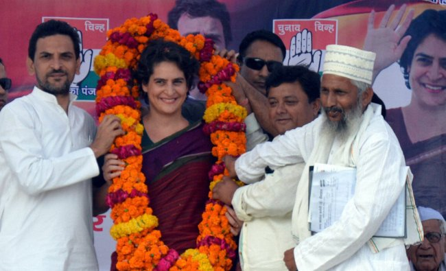 Priyanka Vadra is garlanded during an election campaign rally for her mother and Congress ...