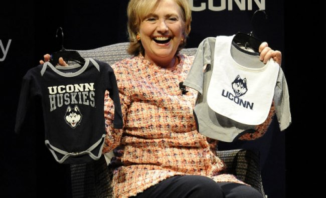 Former Secretary of State Hillary Rodham Clinton holds up UConn Huskies outfits given to her ...