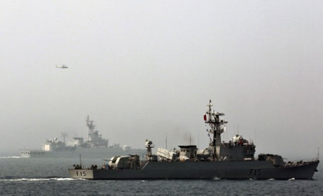 A helicopter flies past as Bangladesh\'s naval frigate BNS Abu Bakar participates in multi-country...