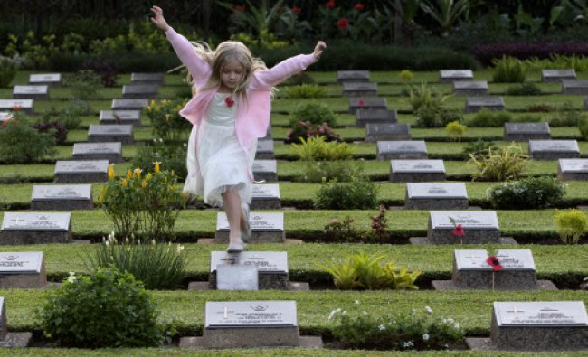 A girl leaps over headstones at the Jakarta War Cemetery following the ANZAC Day dawn service in...