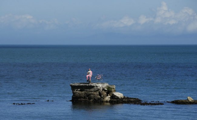 A model of a pink fisherman and bicycle are positioned on a rock in the Irish Sea near the...