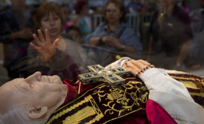 A woman touches the glass box protecting an effigy of Pope John Paul II at the Basilica ...