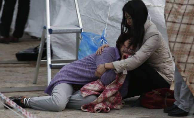 A relative of a missing passenger onboard the capsized Sewol ferry cries at a port in Jindo ...