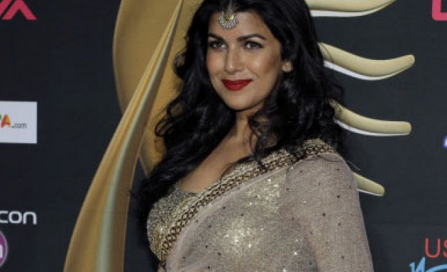 Indian film star Nimrat Kaur poses for photographers as she walks the green carpet for 15th ...