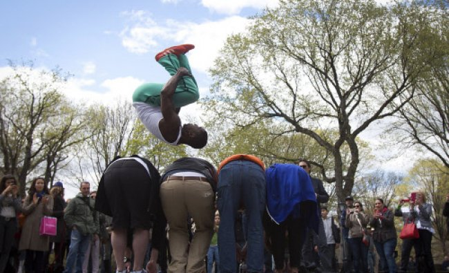 A street performer jumps over four people as part of an impromptu show in Central Park ...