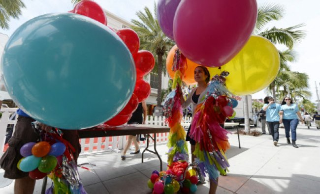 Volunteers decorate Rodeo Drive before the start of a block party to celebrate the 100th ...