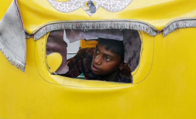 A boy peeps through a window of an auto rickshaw to watch a protest by \'Dalits\' in Ahmedabad ...