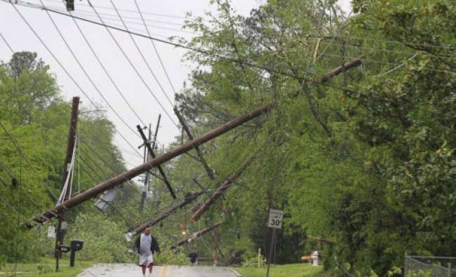 A resident makes his way down Jackson Street and away from the tornado damaged area in Tupelo ...