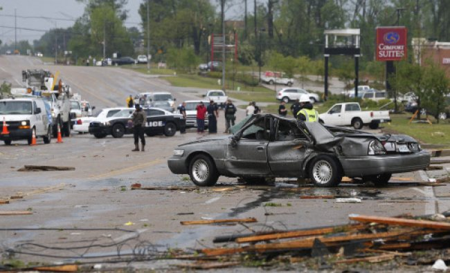 Emergency personnel walk along North Gloster Street after a tornado went through Tupelo ...