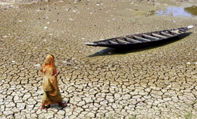 A woman passes by a boat in a dried lake in Dhalai district near India-Bangladesh border...