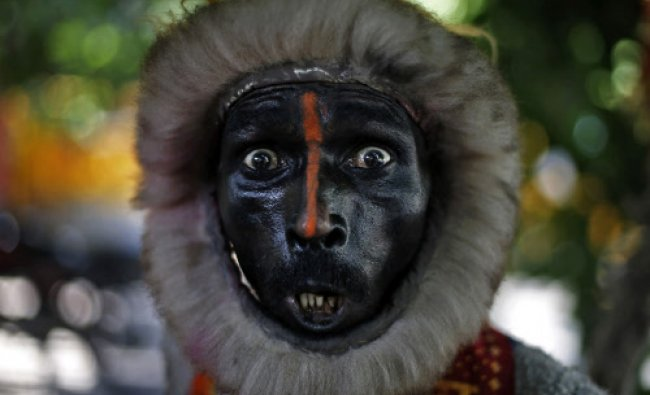 A man dressed as a monkey reacts towards the camera as he begs on a street in New Delhi...