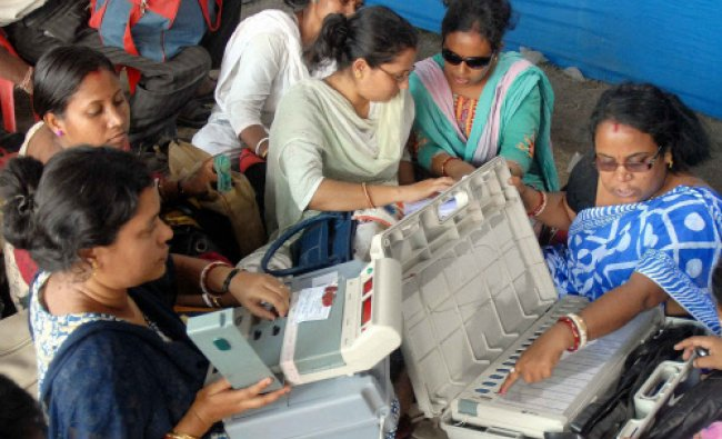 Women polling officials checking the EVMs at voting materials distribution centre...