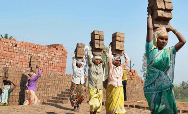 Women laborers work at a brick factory on the eve of International Labor Day in Karad...
