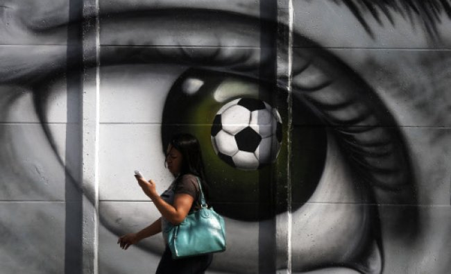 A woman walks past a graffiti of an eye and a soccer ball in Sao Paulo May 5, 2014. The city of...