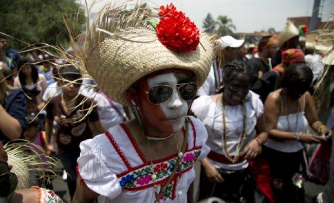 A man dressed as a revolutionary Zacapoaztla Indian female soldier dances during a re-enactment...