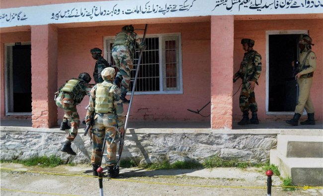 Army personnel inspect a polling station after an IED blast, at Watergam in Baramulla, Kashmir ...