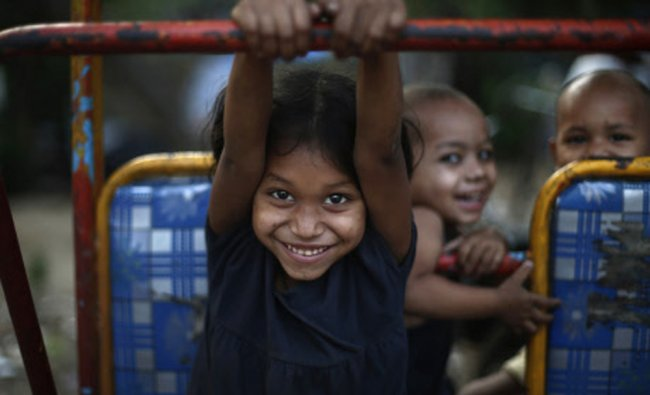Children play on a parked cycle rickshaw outside their home in New Delhi...
