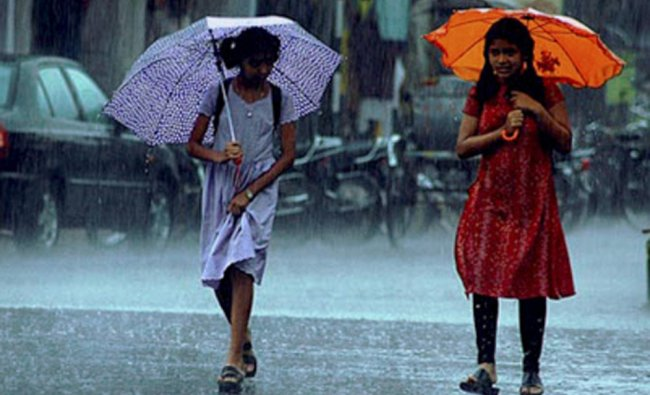 Girls walk on a road with umbrellas as it rains in Nagpur on Tuesday...