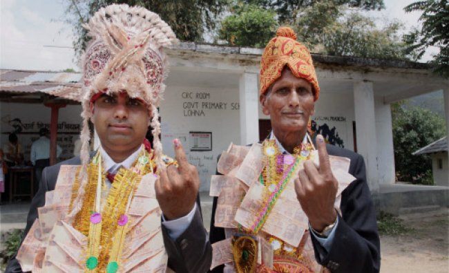 Palampur: A groom and his father show their inked fingers after casting votes for Lok Sabha polls...