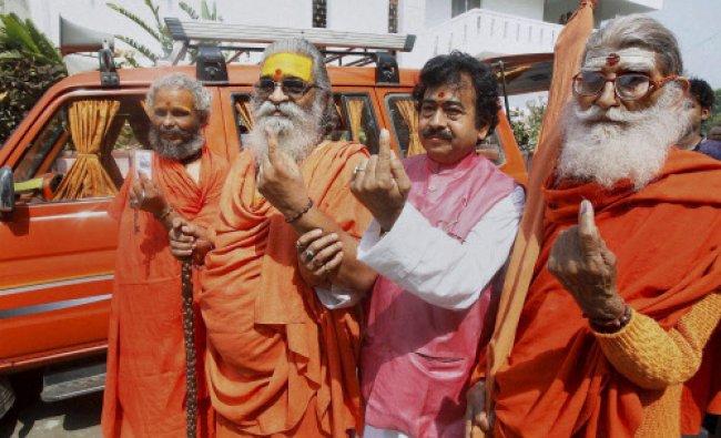 Allahabad: Sankaracharya Swami Vasudevanand Saraswati and other sadhus show their inked fingers ...