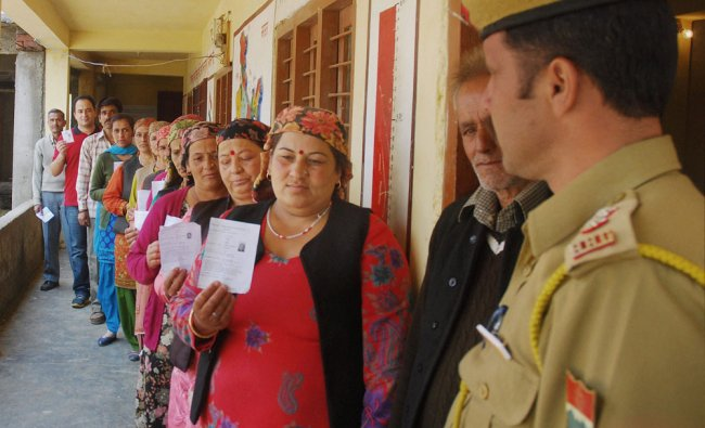 Voters display their identity cards as they wait to cast their votes for Lok Sabha polls ...