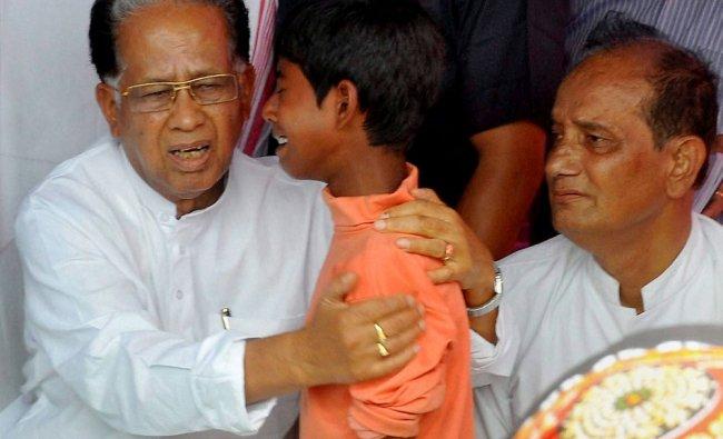 Assam Chief Minister Tarun Gogoi consoles a violence-affected boy at Narayanguri ...