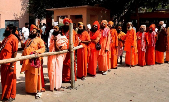 Sadhus wait in a queue to cast their votes for Lok Sabha elections, in Haridwar ...