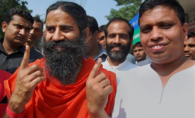 Baba Ramdev and his close aide Acharya Balkrishna shows inked fingers after casting their votes...