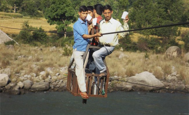 People use a rope-way on their way to cast votes for Lok Sabha polls in Chamba on Wednesday...