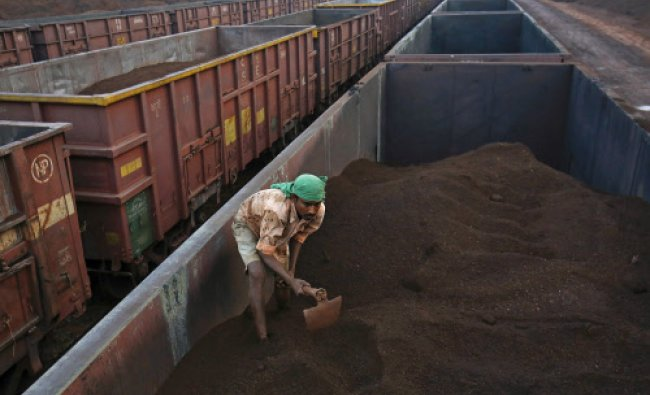 A worker levels the iron ore in a freight train at a railway station at Chitradurga...