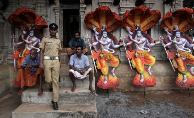 Images of Shiva, meant to be mounted on temple elephants, lean against a temple war during Pooram...