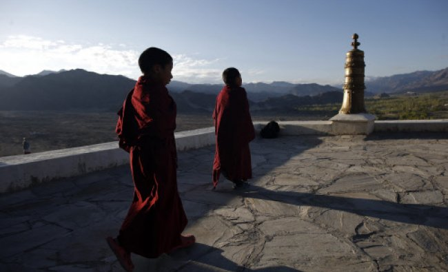 Young Buddhist monks walk on the roof of the Thikse Monastery during early morning in Ladakh...