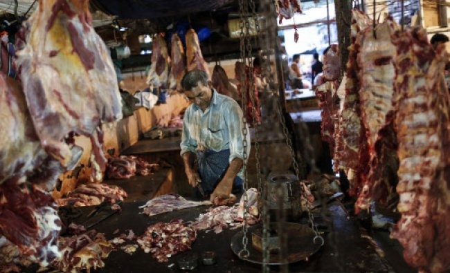 A butcher cuts up portions of beef for sale in an abattoir at a wholesale market in Mumbai...