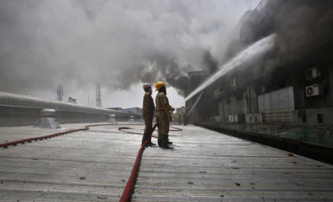 Firefighters try to extinguish a fire that broke out in a plastic factory at Mayapuri industrial...