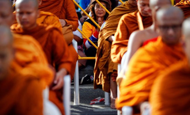 An anti-government protester prays together with Buddhist monks during a mass alms offering...