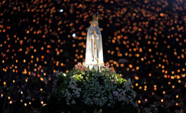 A statue of Our Lady of Fatima is carried during a candle light vigil at the Fatima Sanctuary, in...