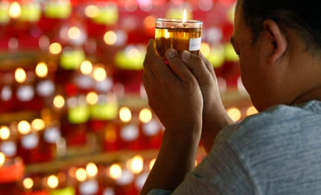 A Buddhist devotee holds an oil lamp as he offers prayers on Wesak Day at the Thai Buddhist...