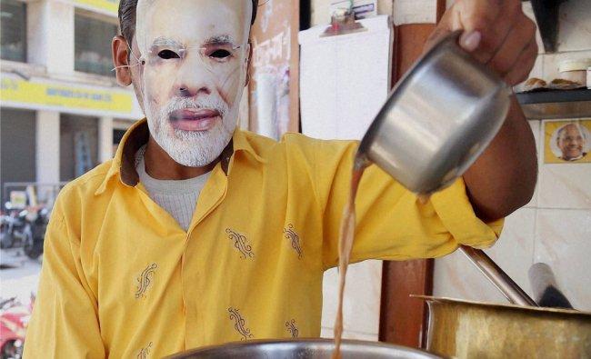 A tea vendor wears the mask of Narendra Modi in Thane, Mumbai ...