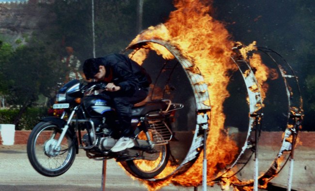 A policeman performs a stunt on a motorcycle during a parade at the Police Training Centre ...