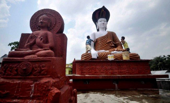 Buddhist devotees cleaning a statue of Lord Buddha on the eve of Buddha purnima, Agartala ...